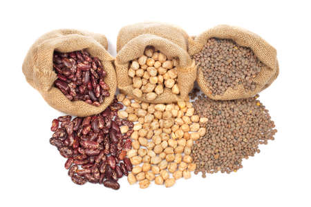 aliment: Lentils, chickpeas and red beans spilling out over a white background. Stock Photo