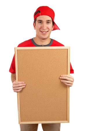 Curious teen with a red cap behind the empty corkboard on white background photo