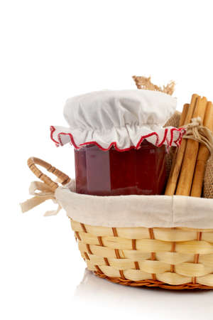 Jam jar, sticks of cinnamon and burlap sac in a basket reflected on white background photo