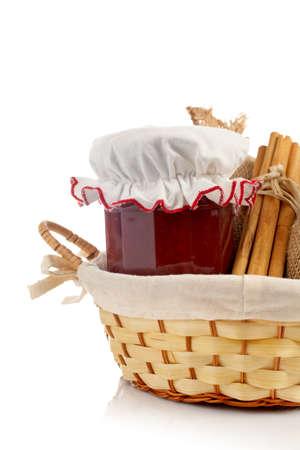 burlap sac: Jam jar, sticks of cinnamon and burlap sac in a basket reflected on white background