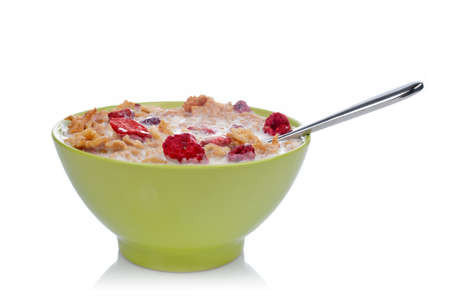 Cornflakes of fruits with the spoon inside the green bowl, reflected on white background. Shallow DOF photo