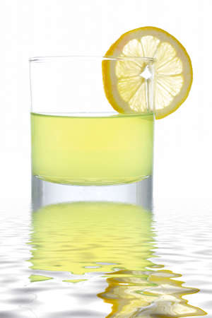 A glass of fresh lemon juice with a slice reflected on the water photo