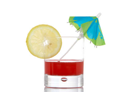 A glass of red juice with a lemon slice and umbrella, reflected on white background photo