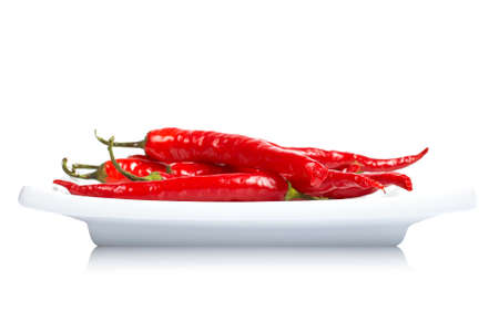 hottest: Red hot chili peppers in the dish, reflected on white background with shallow DOF Stock Photo