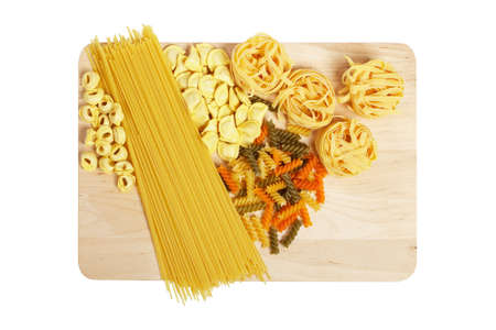 Set of uncooked pasta on wooden plate, isolated on white background photo