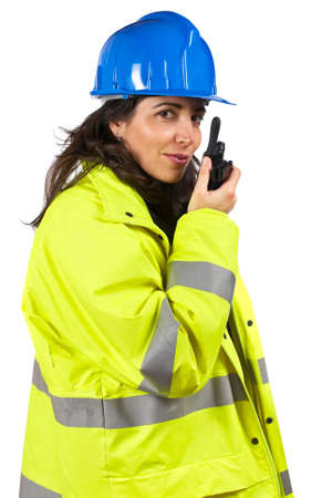 Female construction worker talking with a walkie talkie, over a white background photo