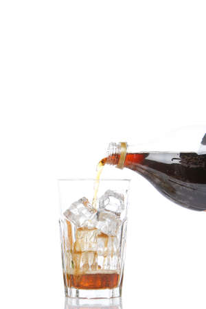 Pouring soda into a glass with ice cubes, reflected on white background with copy space. Shallow DOF photo