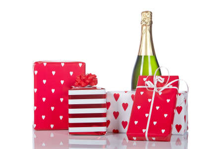 Assortment of gifts and champagne bottle, reflected on white background. Shallow DOF photo