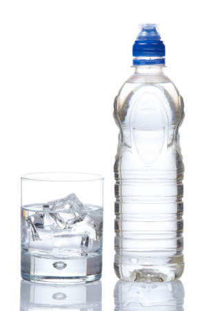 Bottle and glass of mineral water with droplets reflected on white background