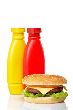Cheeseburger with mustard and ketchup bottles, reflected on white background. Shallow DOF photo