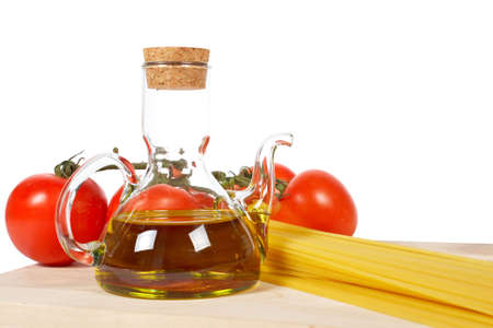 oilcan: Tomatoes, olive oil, garlic and spaghetti, isolated on white background Stock Photo