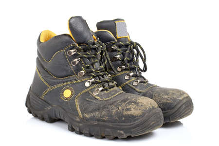 muddy clothes: A pair of old work boots with soft shadow on white background