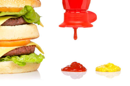 catsup: Double cheeseburger, mustard and pouring ketchup, reflected on white background Stock Photo