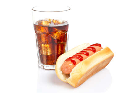 A hot dog and soda glass reflected on white background. Shallow DOF