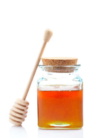 Honey jar and wooden drizzler, reflected on white background