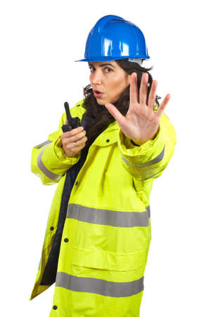 Serious female construction worker talking with a walkie talkie and orders to stop. Eyes on focus photo