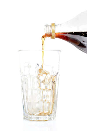 Pouring soda into a empty glass with ice cubes, reflected on white background. Shallow DOF photo