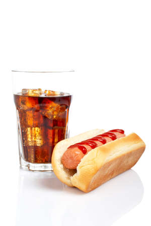 carbonated drink: A hot dog and soda glass, reflected on white background. Shallow DOF