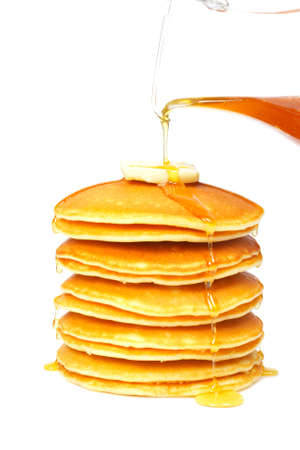Pouring syrup on the big stack of pancakes with butter. Shallow depth of field photo