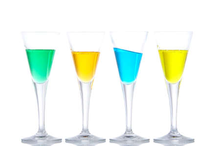 Four glasses with beverages, reflected on white background. Blue on angle. Shallow depth of field Stock Photo - 2685216