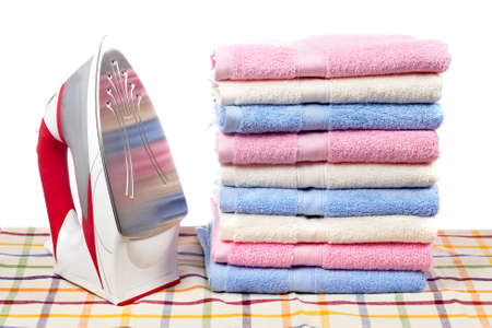 A red electric iron and multicolored towels stacked on squared mat Banco de Imagens - 2744629