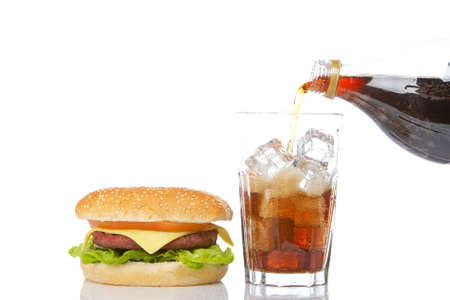 Cheeseburger with lettuce and tomato and pouring soda into a glass with ice cubes, reflected on white background photo