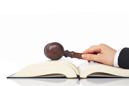 Judge holding a wooden gavel over the law book, reflected on white background
