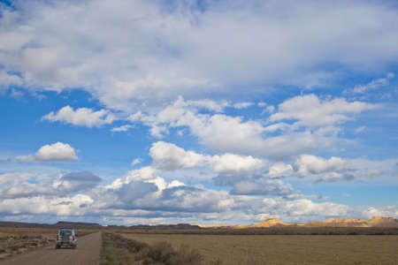 4wd car in the lonely road under the cloudy sky photo
