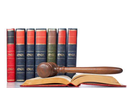 Wooden gavel from the court over the opened law book reflected on white background with space for text. Shallow DOF