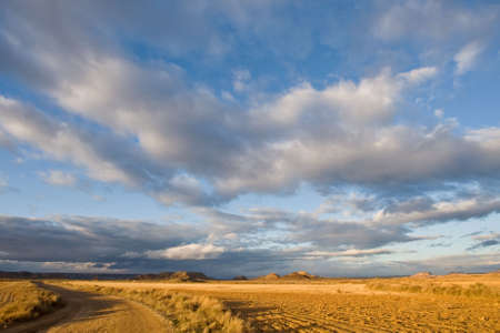 Lonely road to desert under cloudy sky at sunset photo