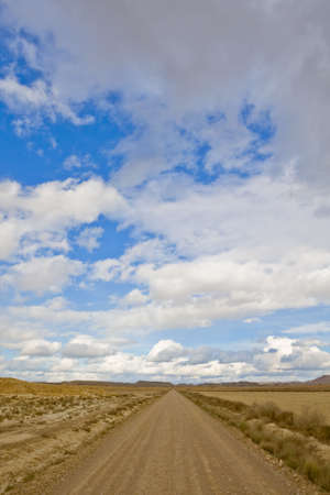 Lonely road to desert under cloudy sky photo
