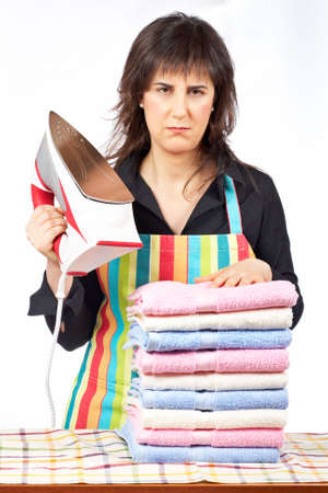 Furious housewife in apron holding a eletric iron close to towels stacked photo