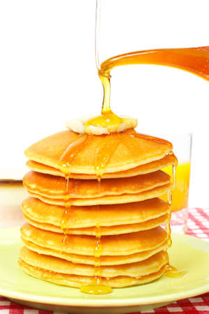 Pouring syrup on the big stack of pancakes with butter. Shallow depth of field