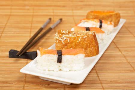 tekka: Sushi on the white plate and chopsticks on bamboo mat.