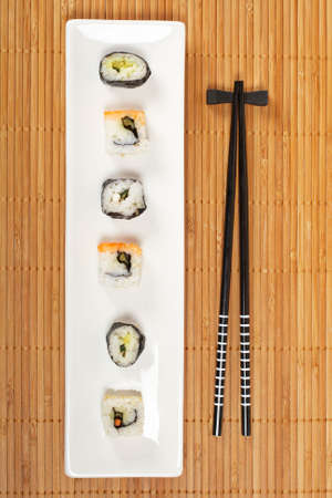 Sushi on the white plate and chopsticks on bamboo mat. Shallow depth of field
