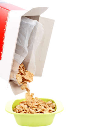 Pouring out cereals in a bowl isolated on white background. Shallow depth of field