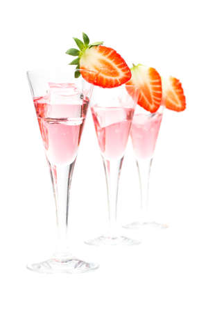 A three glasses of fresh strawberry cocktail with ice cube isolated on white background. Shallow depth of field photo