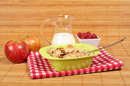 A bowl of cornflakes, milk, two apples and raspberries on bamboo mat photo
