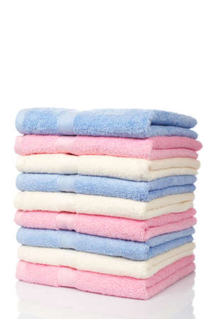 A multicolored towels stacked and reflected on white background