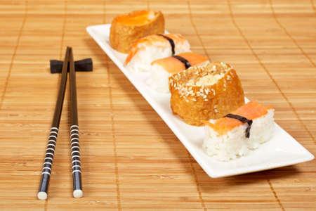 tekka: Sushi on the white plate and chopsticks on bamboo mat. Shallow depth of field