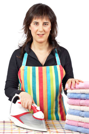 A housewife in apron holding a eletric iron close to towels stacked photo