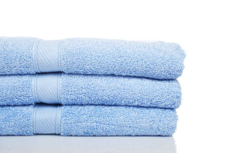 A blue towels stacked reflected on white background Фото со стока