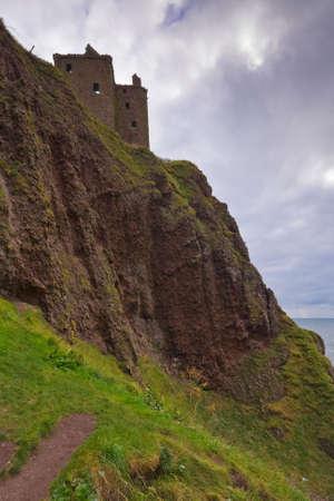 dunnottar castle: Dunnottar Castle under a cloudy sky viewed from below, Scotland Stock Photo