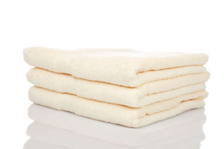 absorb: A yellow towels stacked reflected on white background