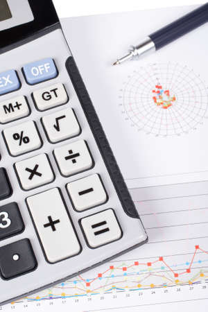 organiser: Calculator and pen on earnings chart background. Shallow depth of field Stock Photo