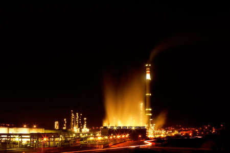 Night view of a petrochemical refinery with chimneys and storage tanks