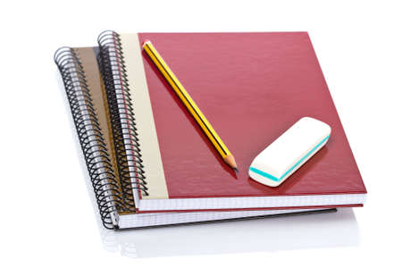 Pencil and eraser on a two notebooks reflected on white background. Shallow depth of field Stock Photo - 3321131