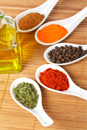 Assortment of spices in the spoons and oil bottle for prepare tasty food with soft shadow in the wooden background. Shallow depth of field Banco de Imagens - 3330811