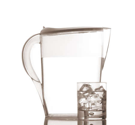 Pitcher and glass with ice cubes of mineral water reflected on white background Stock Photo - 3330814