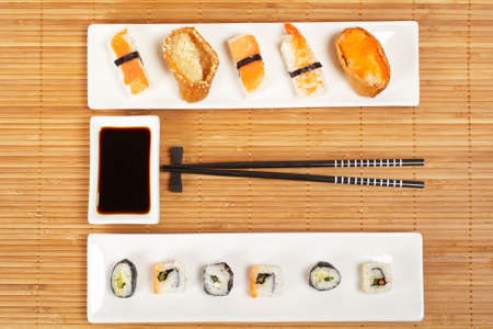 tekka: Sushi on the white plate with soy sauce and chopsticks on bamboo mat. Shallow depth of field